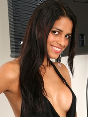Smoldering latina Polliana looking sexy as ever in a tight, open-front black dress showing lots of cleavage, and the dress covers nothing on her back, showing all the way down to her ass crack.