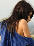 Beautiful young brunett poses in the dark blue dress and nude on panorama of a city